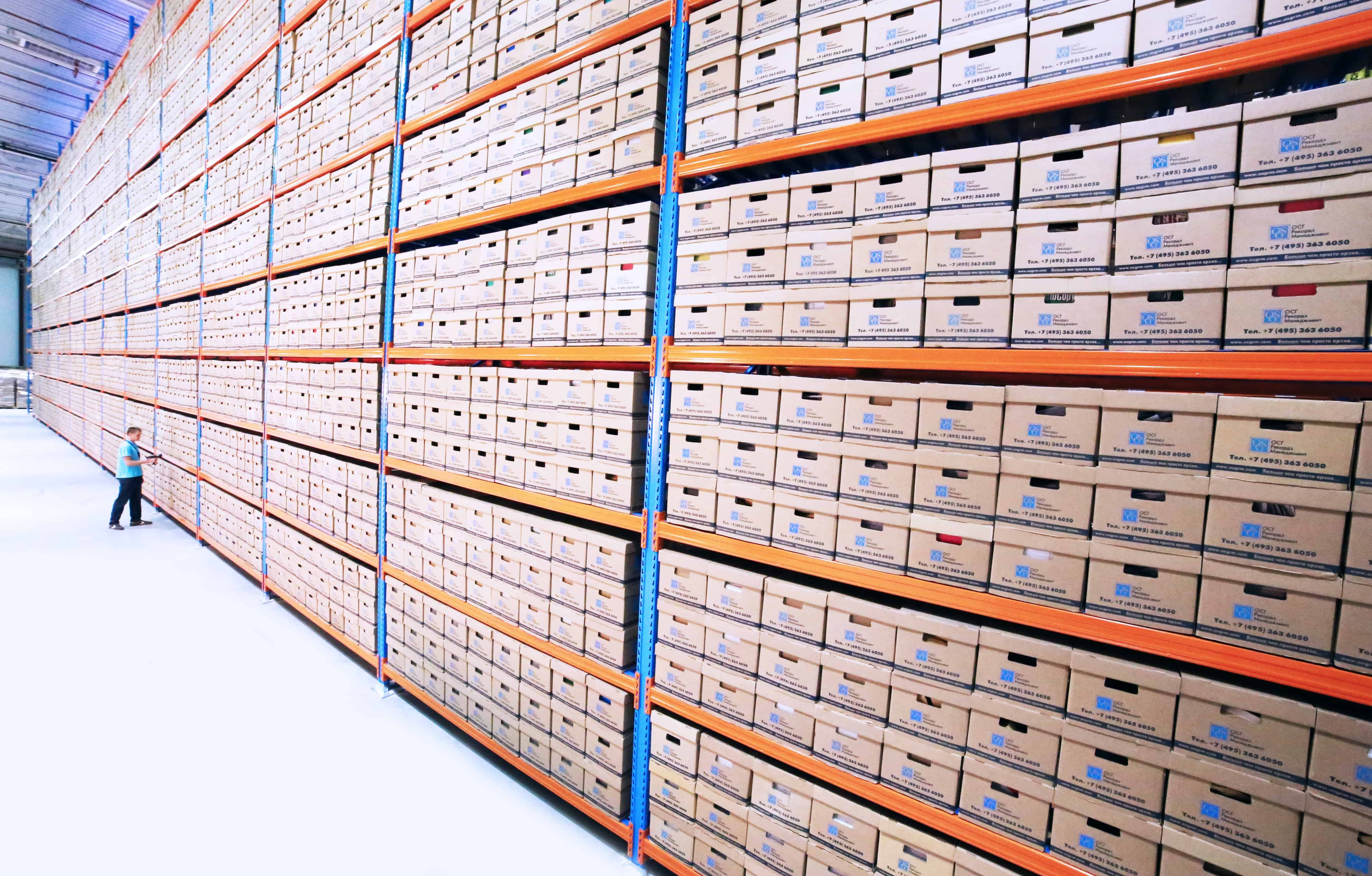 a white painted floor in a warehouse with yellow and blue painted shelves stacked six racks high full of boxes