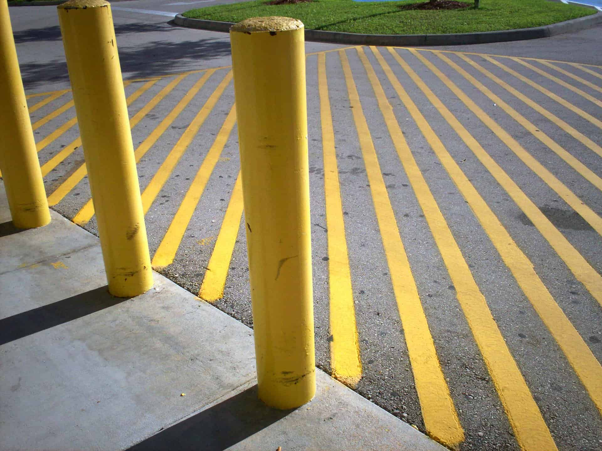 yellow painted lines on concrete in a parking lot with a sidewalk with yellow painted cement posts